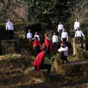 Photo extrait du film comportant des filles en haut rouge et des garçon en chemise blanche.